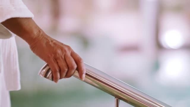 vidéos et rushes de main de femme sur la main courante de piscine - établissement de cure