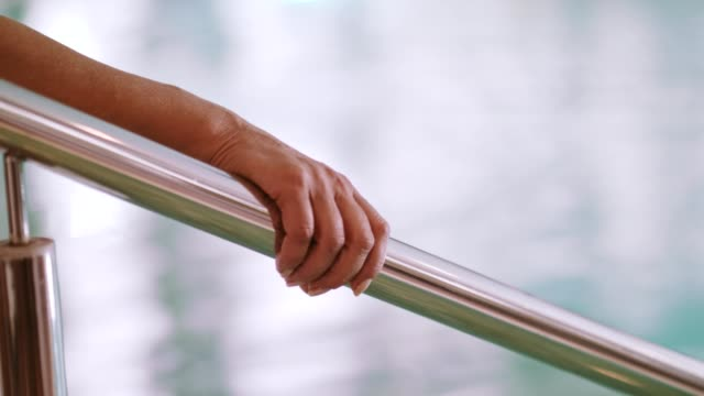 woman's hand on handrail in swimming pool - railings stock videos & royalty-free footage