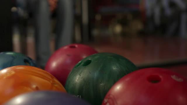 vídeos de stock, filmes e b-roll de cu woman's hand picking up bowling ball off rack / dover, new hampshire, usa - cancha de jogo de boliche