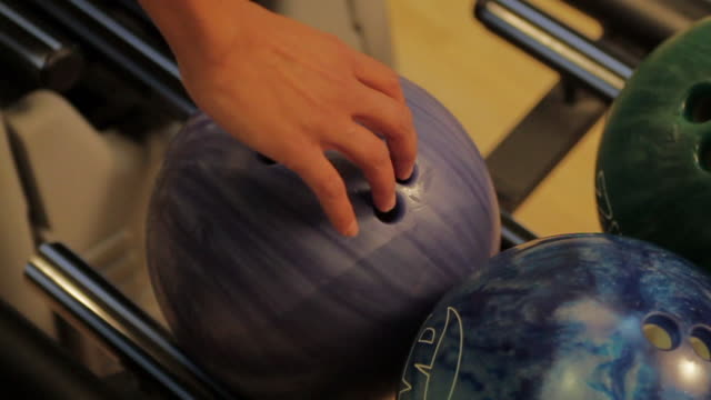 cu woman's hand picking up bowling ball off rack / dover, new hampshire, usa - bowling ball stock videos & royalty-free footage