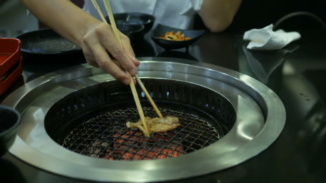 woman's hand pinching grill pork with chopsticks - pinching stock videos & royalty-free footage