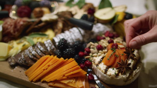 a woman's hand places star anise on an appetizer charcuterie meat/cheeseboard with various fruits, sauces, a chocolate log, and garnishes on a table at an indoor celebration/party - cheese stock videos & royalty-free footage