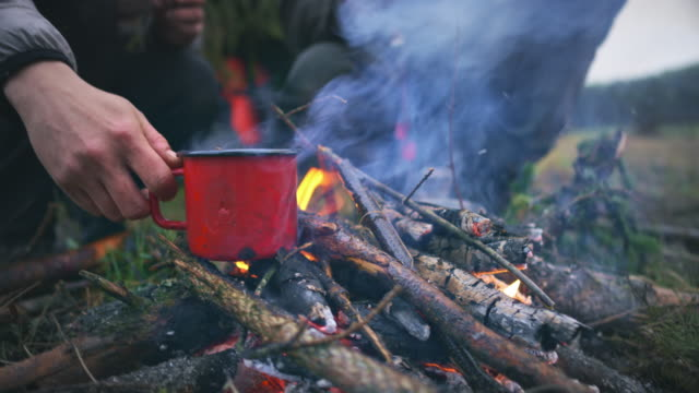 vídeos de stock e filmes b-roll de woman's hand placing a red cup on the twigs in the fire lit in nature - chávena