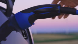 SLO MO Woman's hand plugging an EV plug into her car at dusk