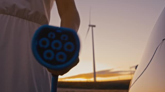 slo mo woman es hand pluging ein ev-stecker in richtung der kamera - station stock-videos und b-roll-filmmaterial