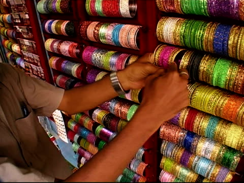Woman's hand pointing to bangles on shelf at bazaar stall / merchant removing bangles off rack and handing to woman / Bangalore, Karnataka, India
