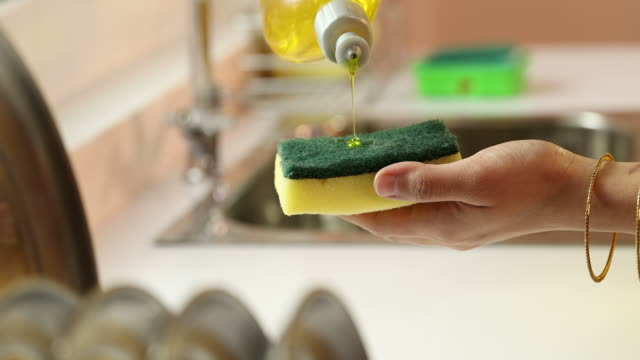 cu woman's hand pouring dishwashing liquid on cleaning sponge / delhi, india - abwaschen stock-videos und b-roll-filmmaterial