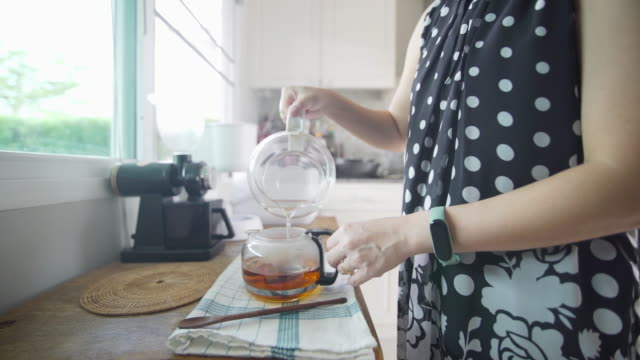 woman's hand pouring tea on the kitchen table at home - dried tea leaves stock videos & royalty-free footage