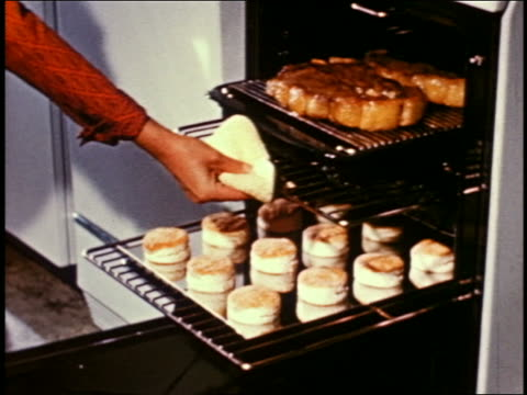 1955 woman's hand pulling tray with thick steaks from oven - 1955 stock-videos und b-roll-filmmaterial