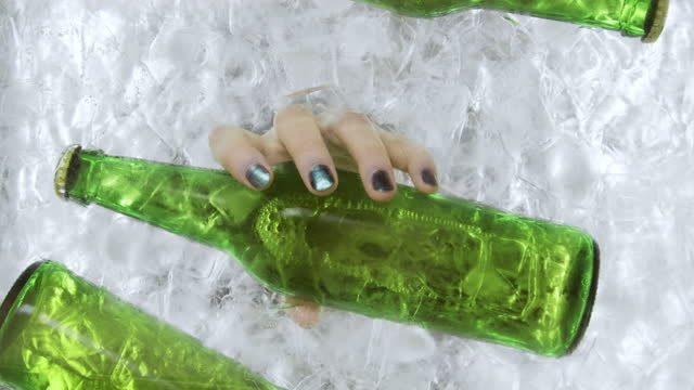 a woman's hand pulls out a green beer bottle from an ice container - cold drink stock videos & royalty-free footage