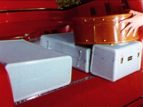 vidéos et rushes de 1965 woman's hand putting piece of luggage on top of others in trunk of mustang / industrial - valise