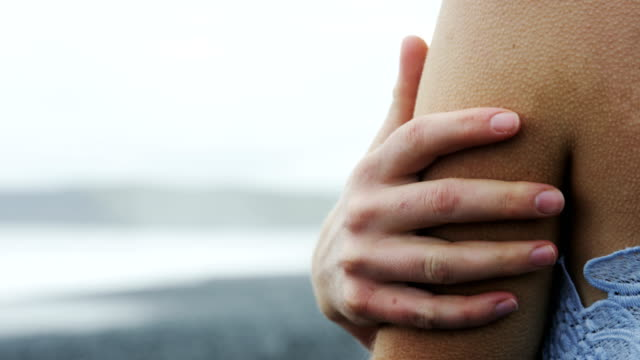 womans hand rubbing arm to keep warm - berühren stock-videos und b-roll-filmmaterial