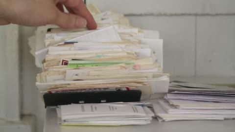cu woman's hand searching through stack of business cards in home office, scarborough, new york, usa - boningsrum bildbanksvideor och videomaterial från bakom kulisserna