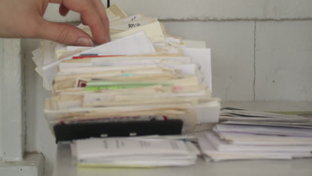 CU Woman's hand searching through stack of business cards in home office, Scarborough, New York, USA