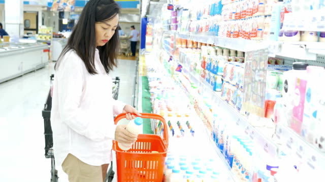 woman's hand shopping dairy product in supermarket
