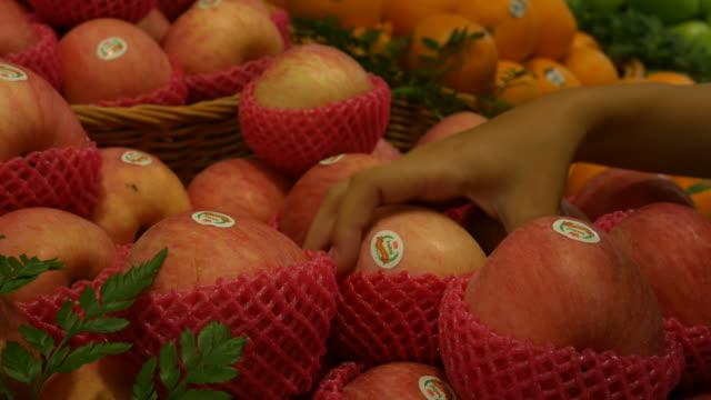 vídeos de stock e filmes b-roll de woman's hand shopping in supermarket - maçã