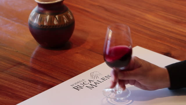 Woman'™s hand swirls red wine at Ruca Malen winery
