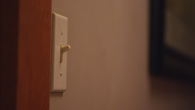 A woman's hand switches a home light switch on and off.