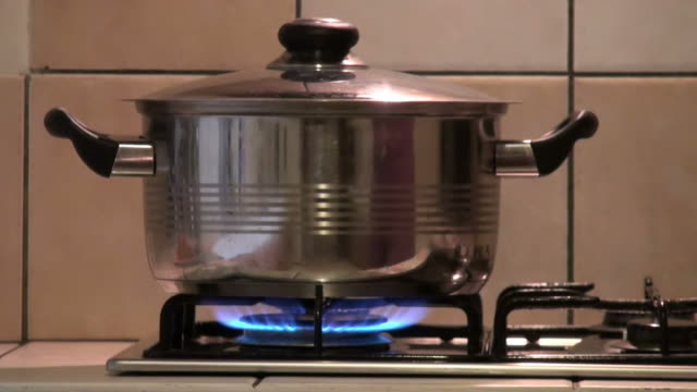 woman's hand taking the lid off from a boiling pot - stove stock videos & royalty-free footage