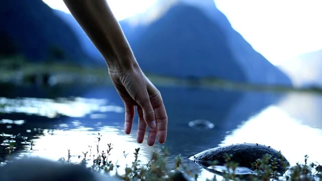 Woman's hand touches lake surface