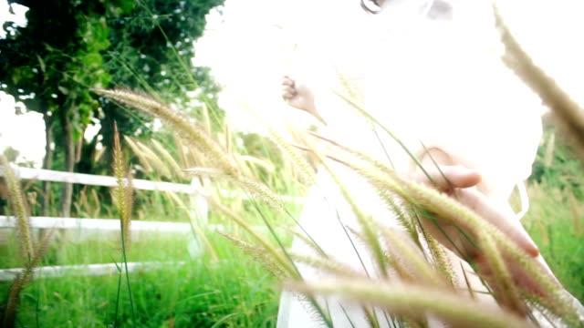Zarte Frauenhand Rasen Blume berühren.