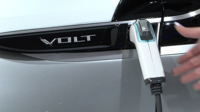 cu woman's hand unplugging cable from chevrolet electric car on display at detroit auto show, detroit, michigan, usa - plugging in stock videos & royalty-free footage