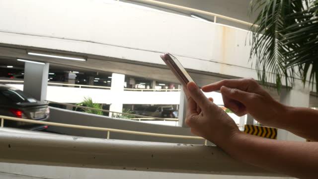 vídeos y material grabado en eventos de stock de mano de la mujer en un teléfono inteligente de estacionamiento - asociación norteamericana de telecomunicaciones e internet