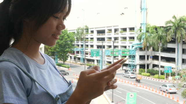 woman's hand using phone in parking lot