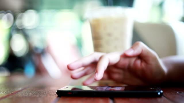 vídeos de stock, filmes e b-roll de mão de mulher usando telefone inteligente no cafe - tapping