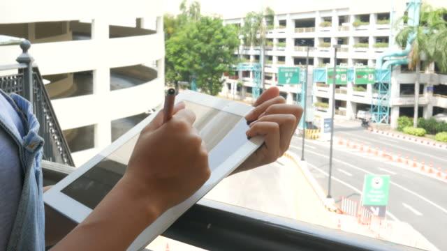 vídeos y material grabado en eventos de stock de mano de mujer con tableta en estacionamiento - asociación norteamericana de telecomunicaciones e internet