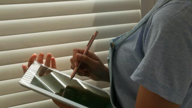 vídeos y material grabado en eventos de stock de mano de la mujer usando la tableta cerca de la ventana - asociación norteamericana de telecomunicaciones e internet