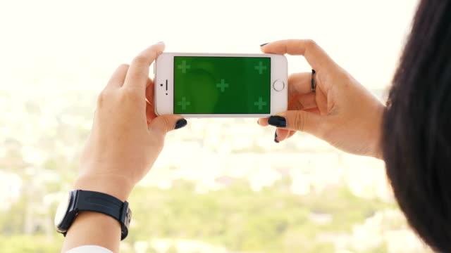 Zarte Frauenhand mit Smartphone für Entspannung mit Chroma-Key-green-Screen-Handy im Garten für Tageszeit