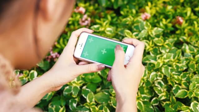 Zarte Frauenhand mit Smartphone für Entspannung mit Chroma-Key-green-Screen-Handy im Garten für Tageszeit Spiel