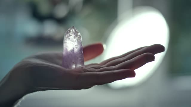 Woman's hand with a healing crystal.
