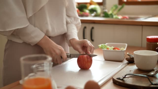 vídeos de stock e filmes b-roll de woman's hand with kitchen knife cutting an apple on cutting board - comida doce