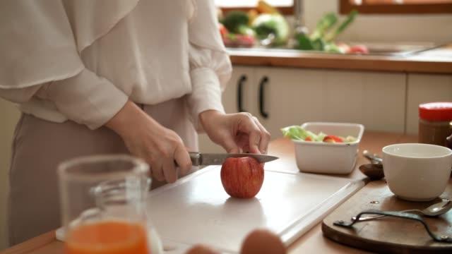 vídeos y material grabado en eventos de stock de mano de mujer con cuchillo de cocina cortando una manzana en la tabla de cortar - dulces