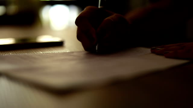 Woman's hand writing a signature, slow motion