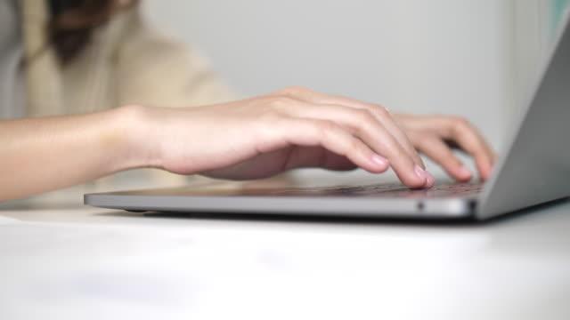 vídeos de stock, filmes e b-roll de as mãos das mulheres estão digitando no teclado do laptop, de perto - portable information device