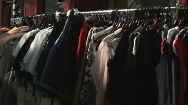 cu pan woman's hands browsing clothes on rack on street, melbourne, victoria, australia - clothes rail stock videos & royalty-free footage
