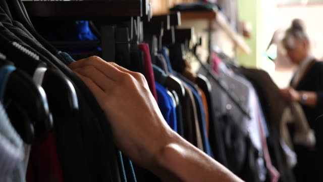 cu womans hands browsing through clothing rack in boutique - negozio di abbigliamento video stock e b–roll