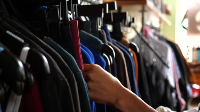 cu womans hands browsing through clothing rack in boutique - clothes rail stock videos & royalty-free footage