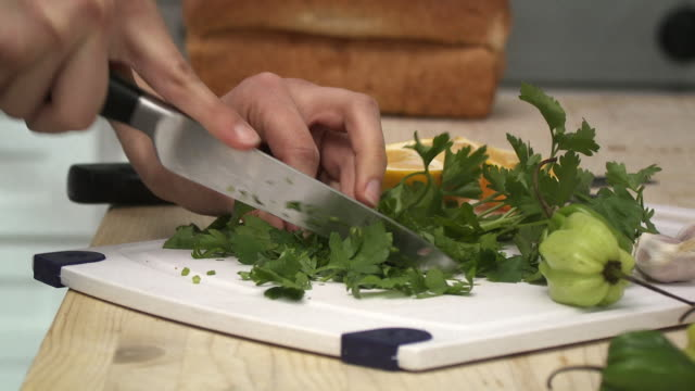 cu woman's hands chopping parsley on kitchen table, scarborough, new york, usa - parsley stock videos and b-roll footage