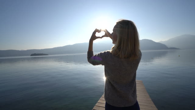Woman's hands create heart shape at lake, sunset