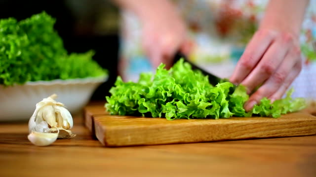 Woman's hands cutting lettuce