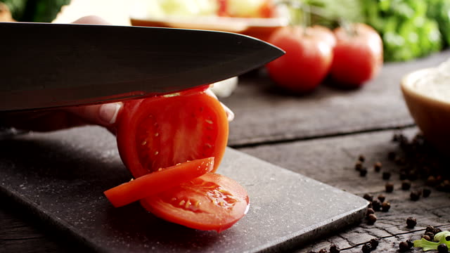 Woman's hands cutting Tomate