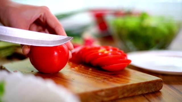 Kvinnans händer skära tomat