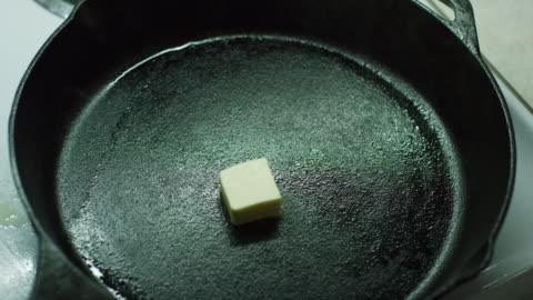vídeos y material grabado en eventos de stock de las manos de una mujer caída pats de mantequilla en un sartén de hierro fundido negro sobre una estufa y revuélvalos con una espátula de madera como los derretimientos de la mantequilla - sartén plana