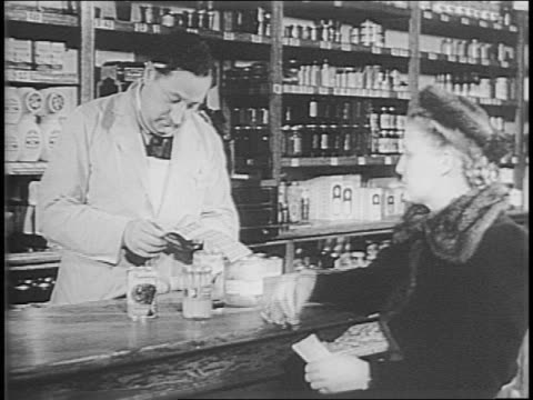 stockvideo's en b-roll-footage met woman's hands flipping pages of open ration book / woman hands ration book to man at grocery store counter / man hands ration book to attendant at... - publicatie