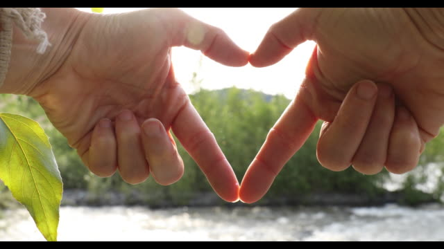 woman's hands form heart shape above cascading river - positive emotion stock videos & royalty-free footage