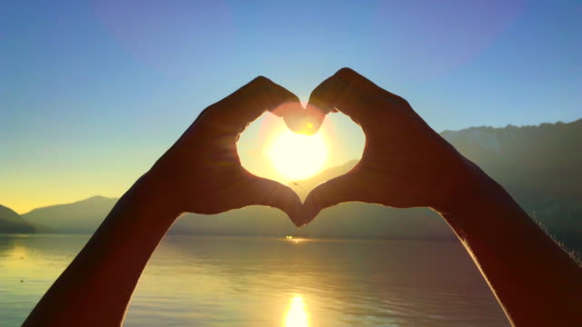 woman's hands form heart shape against sun in sunset and alpine lake with mountain and reflection - illusion stock videos & royalty-free footage